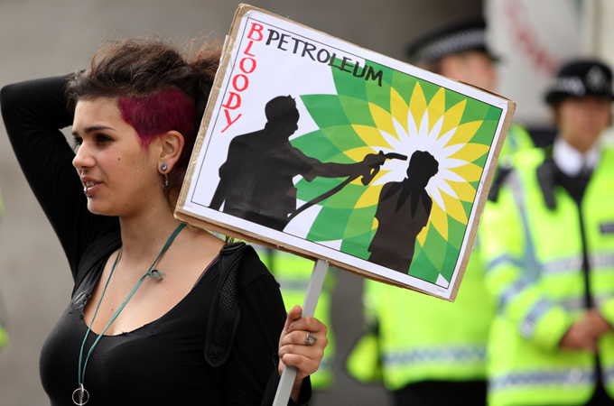 "A woman holding a placard sign saying ""Bloody Petroleum"""